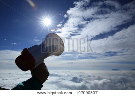 hand hold loudspeaker to sky on mountain peak
