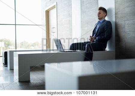 Business man sitting alone on a bench with laptop