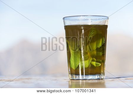 Moroccan mint tea in traditional glass, brewed with a whole plant