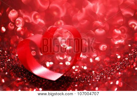 Red ribbon heart on glitter background, Valentines day concept