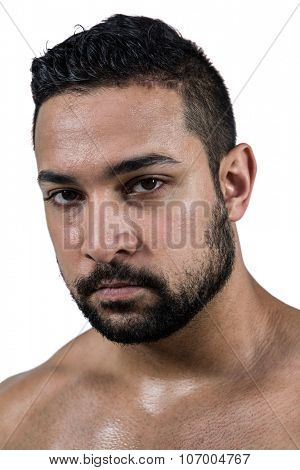 Muscular man frowning at camera on white background