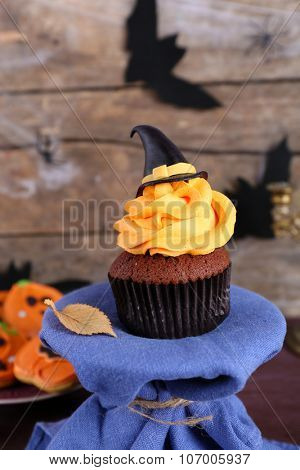 Halloween cupcake and biscuits on table on wooden wall background