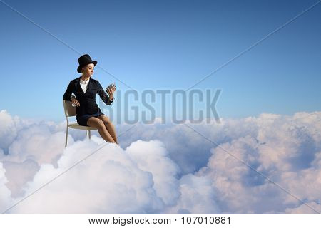 Pretty girl wearing retro hat siting on chair with clock in hand