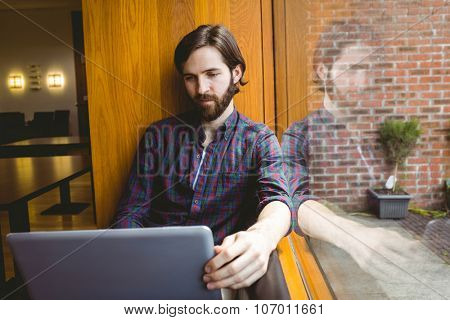 Hipster student using laptop in canteen at the university