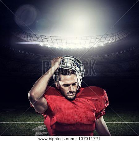 American football player in removing helmet against american football arena
