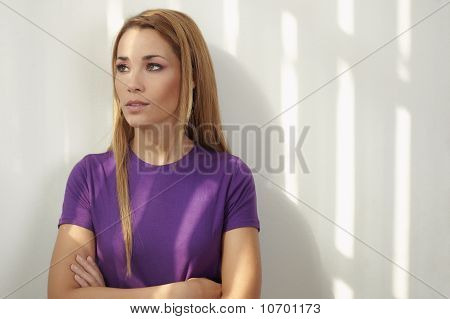 Woman With Arms Crossed On White Wall
