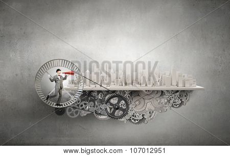 Young businessman running in wheel and screaming emotionally in paper trumpet