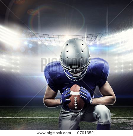 American football player kneeling against american football arena