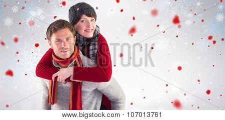 Man giving girlfriend piggy back against snowflake pattern