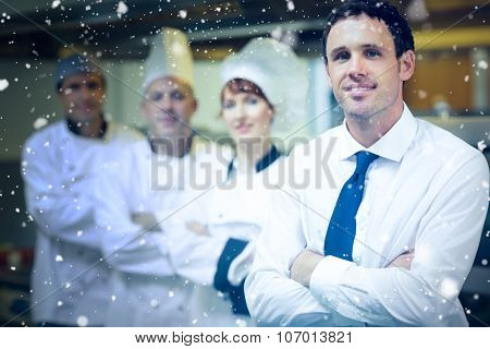 Snow falling against young restaurant manager posing in front of team