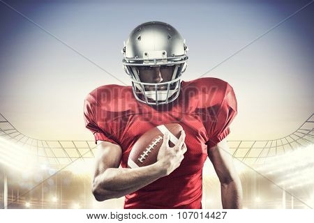 Portrait of confident American football player in red jersey holding ball against rugby stadium