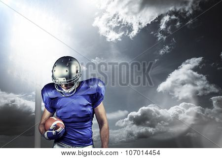 American football player looking down while holding ball against spotlight in sky