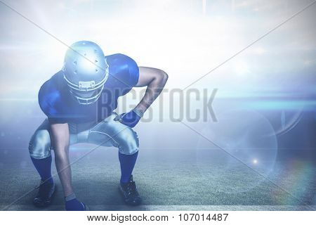 American football player in uniform bending against american football arena