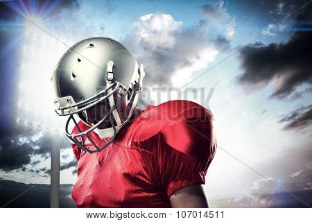 American football player looking down against spotlight in sky