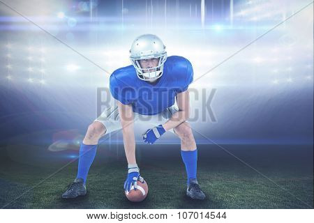 Alert American football player in attack stance against american football arena