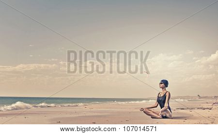 Young woman meditating swimmer in cap and glasses