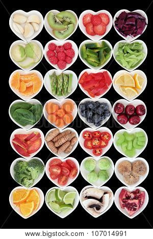 Large health and superfood fruit and vegetable selection in heart shaped dishes over black background.