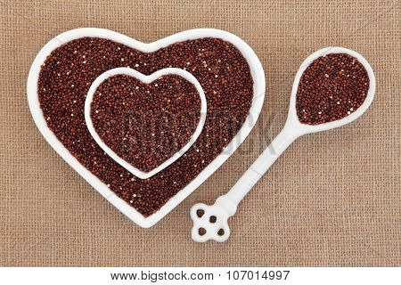 Quinoa grain super food in heart shaped bowls and porcelain spoon over hessian background. Salvia hispanica.