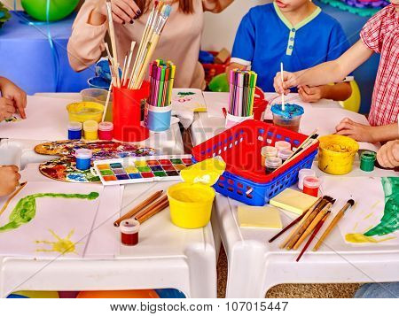 Group kids hands holding colored paper and glue on table in kindergarten .