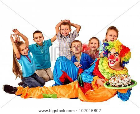 Clown holding cake on birthday with group happy kids. Isolated.