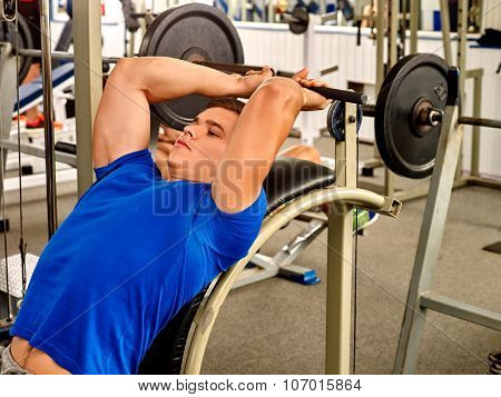 Man in blue clothing working his arms and back at gym. He lying on bench and lifting barbell.