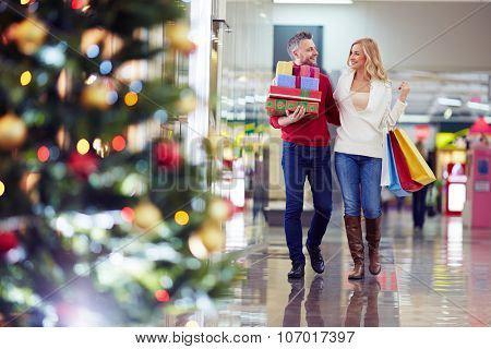 Affectionate couple buying Christmas presents in the mall