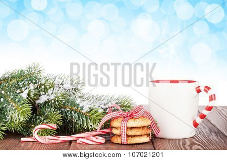 Christmas tree branch, cookies and mulled wine cup with bokeh background