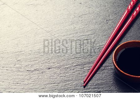 Japanese sushi chopsticks and soy sauce bowl on black stone background. Top view with copy space. Toned