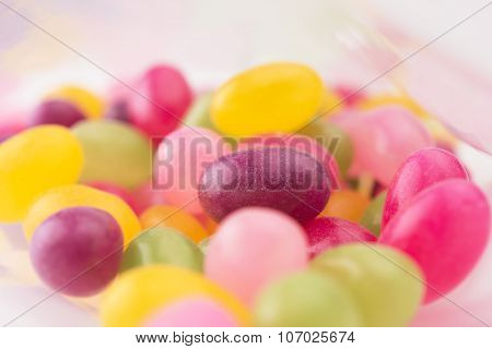 Jelly beans or sugar coated gummy candy inside a plastic bag. Shallow depth of field.