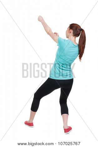 back view of woman in sportswear pulling a rope from the top or cling to something. girl  watching. Rear view people collection.  backside view of person.  Isolated over white background.