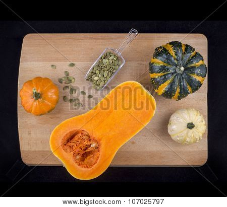 Colorful pumpkins and squash with dried hulled seeds on a wooden table isolated over black
