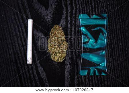 Medical marijuana bud and smoking device on black wood background