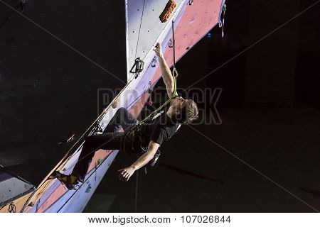 Male athlete makes hard move on climbing wall