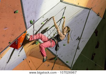 Female extreme climber hanging on arm and feet