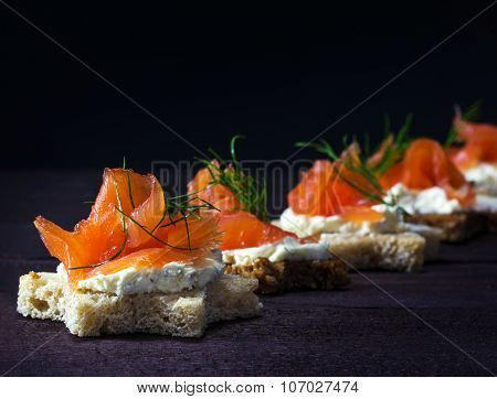 Row Of Festive Canapes In Star Shape With Smoked Salmon On Dark Wood