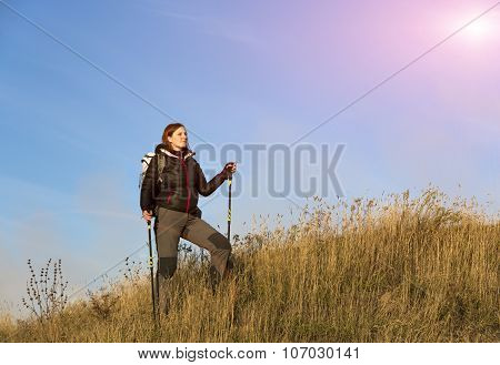 Female hiker walking up on grassy hill