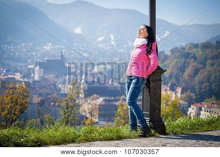 Young woman having a sun bath in autumn. Fashion portrait of pretty girl in cold weather wearing a pink jacket and jeans.