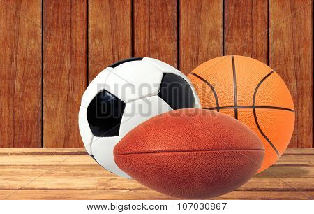 Basketball, Rugby And Soccer Ball On The Wooden Table Over Wooden Background