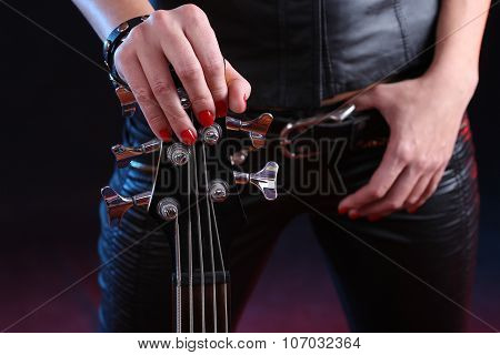 Sexy girl in leather clothes with bass guitar