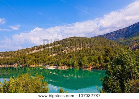 Europe's largest alpine canyon Verdon. Smooth water of the river reflects the wooded shore and cloudy sky