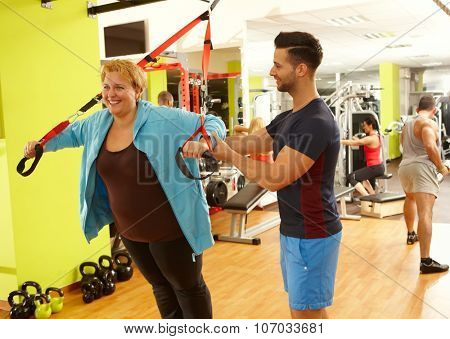 Overweight woman doing suspension training with the guidance of personal trainer.