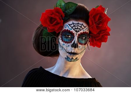 Portrait of scary woman at halloween in mexican santa muerte mask.