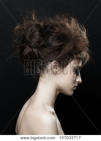 Fashion studio portrait of young beautiful woman with fancy updo hairstyle. Brunette with glamour hairdo. Hair style.