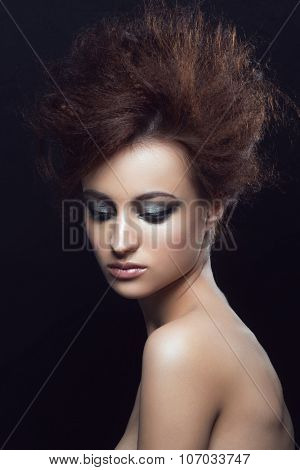 Fashion studio portrait of young beautiful woman with fancy hairstyle and makeup