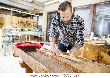 Carpenter sanding a wooden guitar neck in workshop