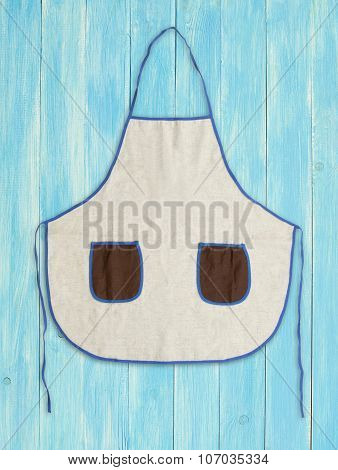 Blank Apron With Pockets On Blue Wooden Background.