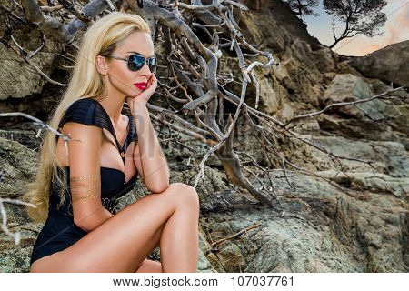 Beautiful blond hair sexy woman young girl model in sunglasses and elegant black swimsuit with cryst