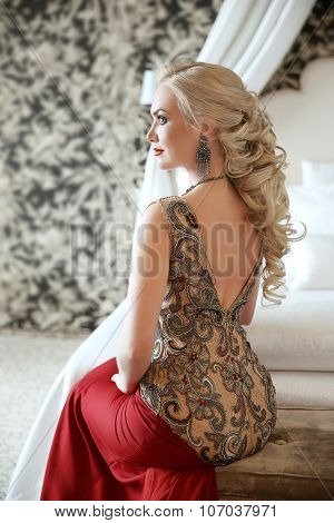 Elegant Hairstyle. Beautiful Blond Woman In Fashion Red Dress Sitting On Modern Sofa At Luxurious In