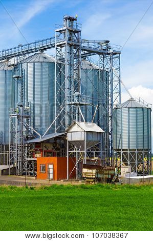 Industrial silos under blue sky, in the field