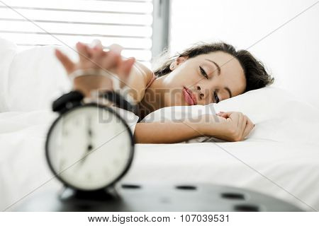 Beautiful young woman waking up with the alarm clock